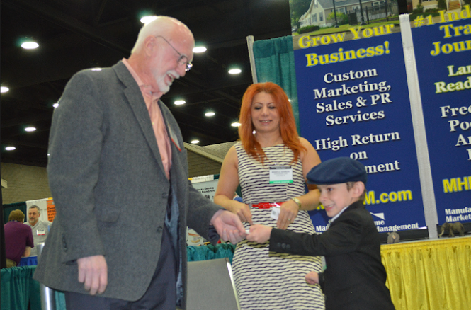 tamas-kovach-right-handing-chet-kearny-business-card-soheyla-kovach-c-mhpronews-com-latonykovach-com-mhc-md-com-2014-louisville-show-booth.png